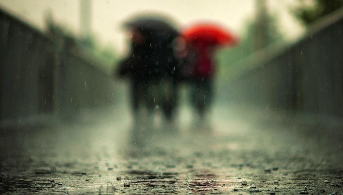 blurred image of people walking in the rain