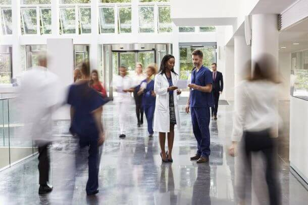 Healthcare professionals standing in a busy hallway, looking at health reports