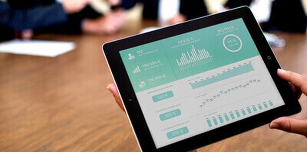 Business meeting with a tablet displaying a corporate dashboard