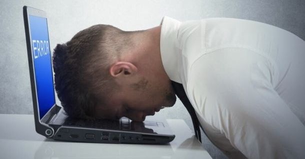 man desperate with face on his laptop's keyboard