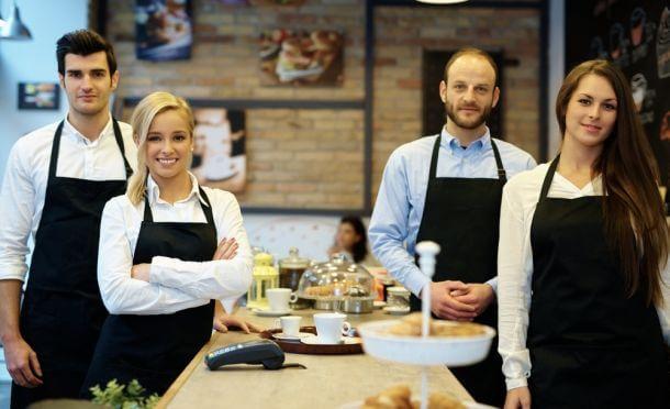 Brigade de cuisine or waiters posing in their restaurant