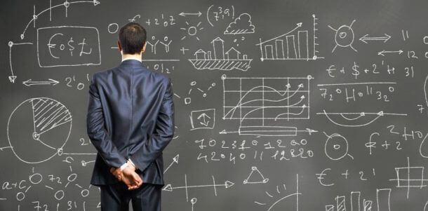 man standing in front of a blackboard with chalk-drawn graphs