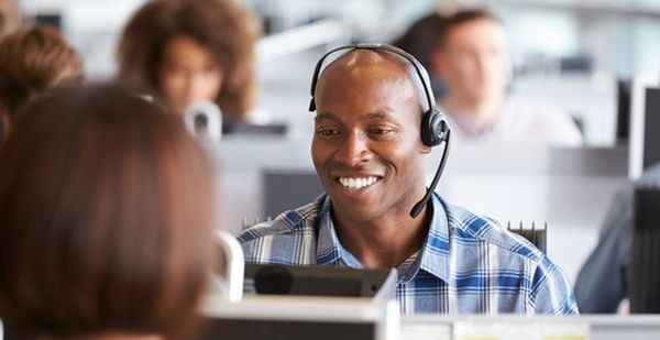 Call center agent sitting at his desk working with a smile